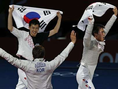 (L-R) South Korea's Bongil Gu, Eunseok Oh and Woo Young Won celebrate with their national flag winning at the end of their men's sabre team gold medal fencing competition against Romania at the ExCel venue at the London 2012 Olympic Games August 3, 2012. Foto: Mike Hutchings / Reuters In English