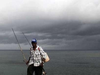 Un pescador camina bajo un cielo nublado a lo largo de las costas de Santo Domingo, República Dominicana. Foto: AP