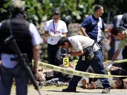 Trabajadores forenses realizan el levantamiento de 17 cadáveres el domingo 16 de septiembre de 2012, en la carretera que une los estados de Michoacán y Guadalajara. Foto: EFE en español