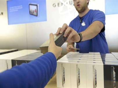 An Apple employee hands out an iPhone 5 at an Apple Store in San Francisco, California, September 21, 2012. Foto: Noah Berger / Reuters In English