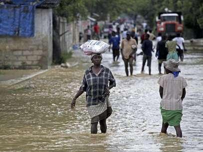 Unas personas caminan por calles inundadas por el huracán Sandy, en La Plaine, Haití, el jueves 25 de octubre de 2012. El huracán dejó al menos 69 muertos en su paso por el Caribe y se dirige a costa este de EEUU.  Foto: The Miami Herald, Carl Juste / AP