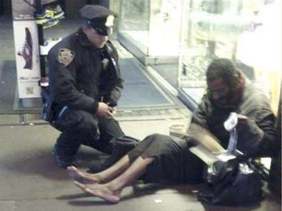 New York police officer Larry DePrimo gives a homeless man a pair of boots and socks in Times Square in this November 14, 2012 handout photo courtesy of Jennifer Foster. The photograph has drawn a deluge of praise after it was published on the police department's Facebook page this week. Foto: Jennifer Foster / Reuters