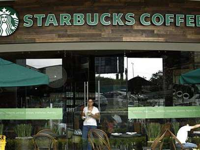 A customer with a cup of coffee leaves the new Starbucks store in San Jose June 20, 2012. Foto: Juan Carlos Ulate / Reuters