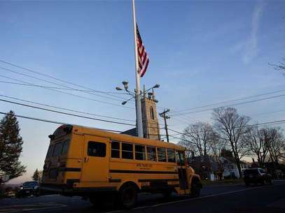 A flag is seen at half mast as a school bus passes along Main Street in Newtown, Connecticut December 14, 2012. Foto: Shannon Stapleton / Reuters