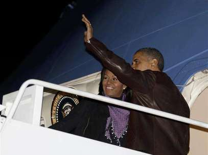 U.S. President Barack Obama waves next to first lady Michelle Obama as they prepare to depart Joint Base Andrews outside Washington, for their holiday trip to Hawaii, December 21, 2012. Foto: Larry Downing / Reuters