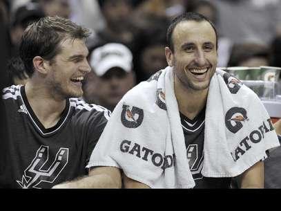 El argentino Emanuel Ginóbili, derecha, y el brasileño Tiago Splitter, de los Spurs de San Antonio, ríen durante la segunda mitad del juego contra los Mavericks de Dallas, el domingo 23 de diciembre de 2012, en San Antonio.  Foto: Darren Abate / AP