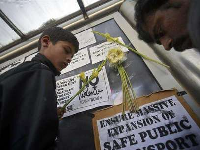 Demonstrators put flowers on the billboard of a bus stop during a protest march in New Delhi December 29, 2012. Foto: Danish Siddiqui / Reuters