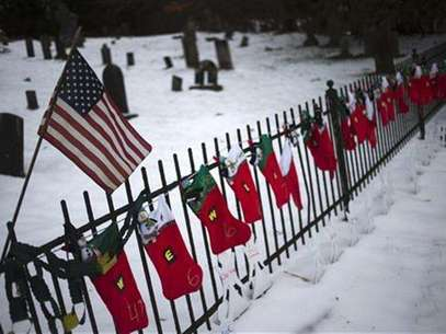 A U.S. flag hangs over stockings left as a memorial for victims of the Sandy Hook Elementary School shooting, along a fence surrounding the Sandy Hook Cemetery in Newtown, Connecticut December 27, 2012. Foto: Adrees Latif / Reuters