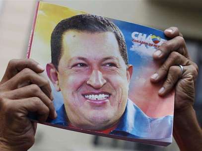 A Venezuelan man holds a picture of Venezuela's President Hugo Chavez during a mass to pray for his recovery at a church in Havana January 12, 2013. Foto: STRINGER / Reuters