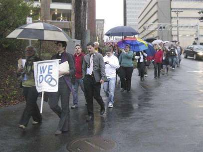 """Same-sex couples and their supporters marched through the streets of downtown Winston-Salem, North Carolina, January 14, 2013 after seeking marriage licenses that they knew they would be denied. They sang """"as long as it takes, love won't be denied"""" as they walked in the rain. Holding the """"We Do"""" sign at the front is Jasmine Beach-Ferrara, executive director of the Campaign for Southern Equality, which is leading the """"We Do"""" push for marriage equality in seven Southern states in January. She also is a minister in the United Church of Christ. Foto: Colleen Jenkins / Reuters"""