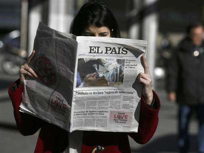 "A woman poses with a copy of the January 24 first edition of Spanish newspaper El Pais in central Madrid January 24, 2013. Spain's influential El Pais newspaper withdrew what it said was ""false photo of Hugo Chavez"" that it had published in its on-line and print editions on Thursday. Foto: Andrea Comas / Reuters"