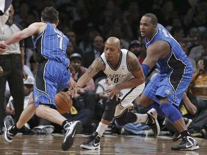 Brooklyn Nets forward Keith Bogans (10) cuts between Orlando Magic guard J.J. Redick (7) and forward Glen Davis (11) to steal the ball in the fourth quarter of their NBA basketball game in New York, January 28, 2013. Foto: Ray Stubblebine / Reuters