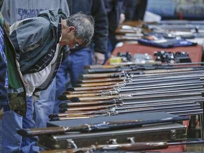 Un posible cliente observa escopetas durante una muestra de armas en el Centro de Convenciones Plaza Empire State en Albany, Nueva York, el 26 de enero de 2013. Cuatro senadores intentan alcanzar una solución negociada para ampliar el requisito sobre la verificación de los antecedentes a quienes quieran poseer un arma.  Foto: Philip Kamrass / AP