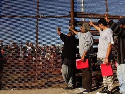 A group of recently deported immigrants stand near the double steel fence that separates San Diego and Tijuana at the border in Tijuana December 10, 2011. Foto: Jorge Duenes / Reuters