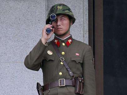 A North Korean soldier looks south through a pair of binoculars on the north side of the truce village of Panmunjom in the demilitarised zone separating the two Koreas in Paju, about 55 km (34 miles) north of Seoul, August 25, 2010. Foto: Jo Yong-Hak / Reuters