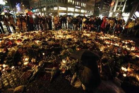 Un grupo de personas se protegen de la lluvia con sus paraguas mientras recuerdan con velas y flores a las víctimas de la masacre ocurrida en Noruega. Foto: Wolfgang Rattay / REUTERS