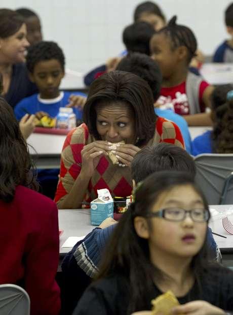La primera dama Michelle Obama come un taco de pavo junto a varios niños en la escuela primaria Parklawn en Alexandria, Virginia.  Foto: Pablo Martínez Monsiváis / AP