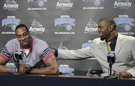 El pivote Dwight Howard recibe una palmada del gerente general del Magic, Otis Smith, durante una rueda de prensa el jueves 15 de marzo de 2012 en Orlando. Howard firmó el mismo jueves los documentos para dejar de lado la opción de terminar anticipadamente su contrato con el Magic, y seguir con el equipo al comenzar la temporada 2012-13.  Foto: John Raoux / AP