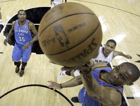 Russell Westbrook, del Thunder de Oklahoma City, encesta ante la mirada de su compañero Kevin Durant (35) y el jugador de los Spurs de San Antonio Gary Neal (14) durante la primera mitad del Juego 5 de la serie por el campeonato de la Conferencia del Oeste de la NBA el lunes 4 de junio de 2012, en San Antonio. El Thunder venció 108-103 a los Spurs para tomar una ventaja de 3-2 en la serie.  Foto: Eric Gay / AP