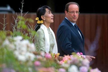 ARCHIVO - En esta foto del 26 de junio del 2012, la líder opositora de Mianmar Aung San Suu Kyi y el presidente francés Francois Hollande caminan por el Palacio del Elíseo en París. Multitudes jubilosas recibieron el sábado a Suu Kyi en Mianmar a su regreso de su gira por Europa, donde ganó un apoyo entusiasta para su papel en la transición democrática en su país y fue celebrada como una jefa de estado.  Foto: Bertrand Langlois, Pool  / AP