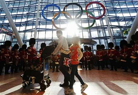 Travellers pass the Olympic Rings during an unveiling ceremony in the Terminal Five arrivals hall at Heathrow Airport, in preparation for the London 2012 Olympic Games in London June 20, 2012. Foto: Luke MacGregor / Reuters In English