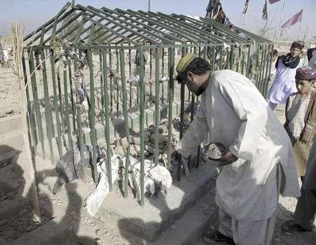 Un hombre recoge algunas pertenencias de las víctimas en el lugar donde estalló una bomba en un cementerio en Lashkar Gah, al suroeste de Kabul, Afganistán, el domingo 19 de agosto de 2012. Dos hermanos de un legislador perecieron en el atentado. Otros siete integrantes de la familia que visitaba una tumba resultaron heridos en el cementerio, dijo la policía.  Foto: Abdul Khaleq / AP