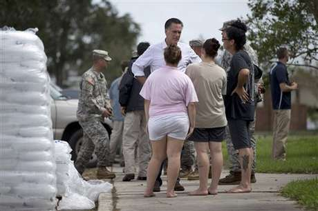 Mitt Romney habla con personas que sufrieron inundaciones por el huracán Isaac. Foto: AP