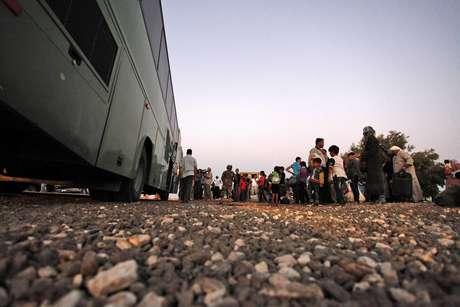 Refugiados sirios recién llegados forman fila para ser llevados por un autobús militar al Campamento de Refugiados de Zaatari en la ciudad de Mafraq (Jordania) Foto:  Mohammad Hannon / AP