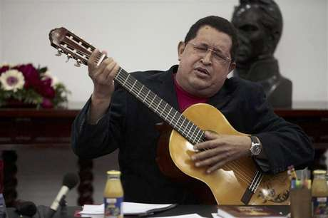 Venezuelan President Hugo Chavez plays a guitar, which was a gift from Mexican singer Vicente Fernandez, during a cabinet meeting at Miraflores Palace in Caracas September 20, 2012. Foto: Miraflores Palace / Reuters In English
