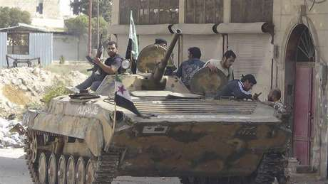 Members of the Free Syrian Army are seen around a captured Syrian Army tank after clashes, at Marat al-Numan, near the northern province of Idlib October 9, 2012. Picture taken October 9, 2012. Foto: Shaam News Network / Reuters In English