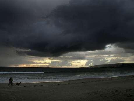 Una pareja pasea su perro en la playa el lunes 15 de octubre de 2012, en Ensenada, estado mexicano de Baja California, donde se esperan lluvias debido a la aproximación de 'Paul'. Foto: EFE en español