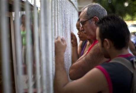 Cubanos averiguan sobre la nueva disposición para salir del país en una oficina de migración de La Habana. Foto: AP