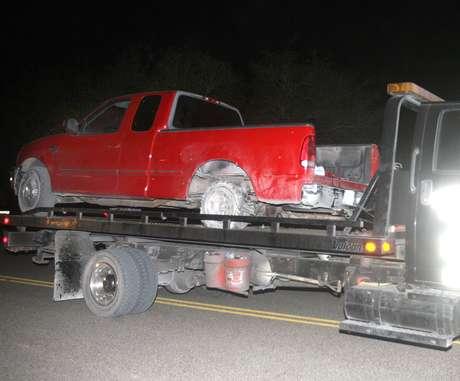 Una camioneta pick up es retirada del lugar donde fue baleada desde un helicóptero por un policía estatal durante una persecución cerca de La Joya, Texas, el jueves 25 de octubre de 2012. Foto: AP
