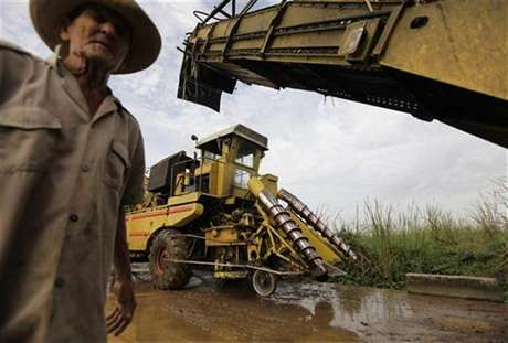 A farmer walks beside two combined harvesters being serviced after cutting sugar cane in the fields near the village of Viana, province of Villa Clara in central Cuba in this file photo taken February 24, 2010. Foto: Desmond Boylan / Reuters