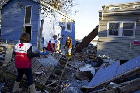 Red Cross volunteers Jessica Elam and Gilbert Abney check on Rob Fragetti, who is attempting to salvage items with his neighbors in their destroyed homes, in this handout photo from the American Red Cross, in Staten Island, New York, in this November 6, 2012 file photo. Foto: Talia Frenkel / Reuters
