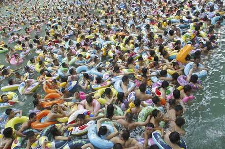 Residents crowd in a swimming pool to escape the summer heat during a hot weather spell in Daying county of Suining, Sichuan province in this July 4, 2010 file picture. China is mulling changes to its one-child policy, a former family planning official said, with government advisory bodies drafting proposals in the face of a rapidly ageing society in the world's most populous nation. Proposed changes would allow for urban couples to have a second child, even if one of the parents is themselves not an only child, the China Daily cited Zhang Weiqing, the former head of the National Population and Family Planning Commission, as saying on November 28, 2012. Foto: Stringer / Reuters