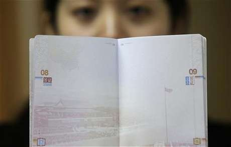 A woman holds a Chinese passport, displaying a Chinese map which includes an area in the South China Sea inside a line of dashes representing maritime territory claimed by China (L, top) and a picture of Beijing's Tiananmen Square (bottom), at an office in Wuhan airport, Hubei province, November 23, 2012. The Philippines and Vietnam condemned Chinese passports containing a map of China's disputed maritime claims on Thursday, branding the new design a violation of their sovereignty. Foto: Stringer / Reuters