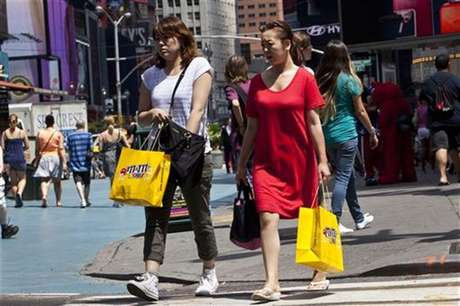 Women carry shopping bags through Times Square in New York, July 27, 2012. Foto: Andrew Burton / Reuters