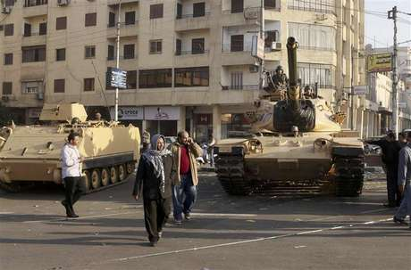 Supporters of the Muslim Brotherhood walk past tanks that were just deployed outside the Egyptian presidential palace in Cairo December 6, 2012. At least three tanks are deployed outside the palace on Thursday in a street where supporters and opponents of President Mohamed Mursi had been clashing into the early hours of the morning, a Reuters witness said. Foto: Asmaa Waguih / Reuters
