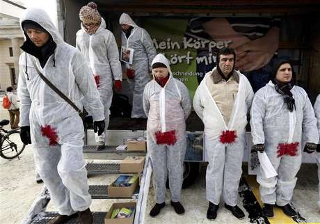 Protestors wearing overalls daubed with red paint on the genital area, demonstrate against male circumcision, in front of the Brandenburg Gate in Berlin December 12, 2012. Foto: Pawel Kopczynski / Reuters