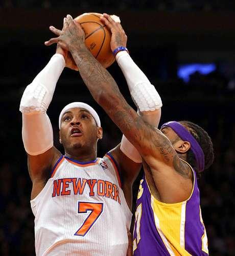 Jordan Hil intenta bloquear el disparo de Carmelo Anthony (7). Foto: Kathy Willens / AP