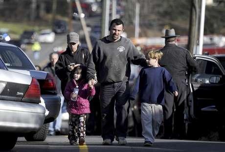 Un padre acompaña a sus hijos mientras policías estatales aseguran la zona donde ocurrió un tiroteo en la Escuela Primaria Sandy Hook, en Newtown, Connecticut, que dejó 27 muertos, 20 de ellos niños, el viernes 14 de diciembre de 2012.  Foto: Jessica Hill / AP