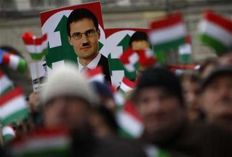A defaced photo of Marton Gyongyosi, a leader of Hungary's far-right political party Jobbik, is seen on a placard during a demonstration against Nazism in front of the Parliament building in Budapest December 2, 2012. Foto: Bernadett Szabo / Reuters