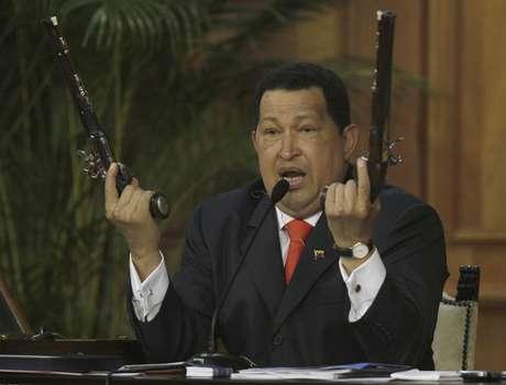 El presidente Hugo Chávez sostiene un par de pistolas que afirma pertenecieron al héroe de la independencia venezolana Simón Bolivar durante una ceremonia por el 229 aniversario del nacimiento del prócer efectuada en el palacio de Miraflores, en Caracas, en esta fotografía de archivo del 24 de julio de 2012.  Foto: Fernando Llano / AP