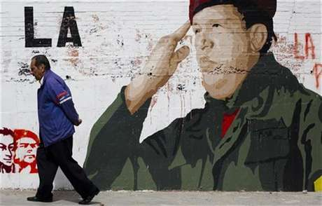 "People talk in front of a mural in Caracas January 2, 2013. Venezuelan President Hugo Chavez is aware that his condition is complicated following a fourth cancer operation in Cuba, Vice President Nicolas Maduro said on Tuesday, as the OPEC nation watches for clues to the socialist leader's health. The words read, ""Chavez, heart of my country"". Foto: Carlos Garcia Rawlins / Reuters"