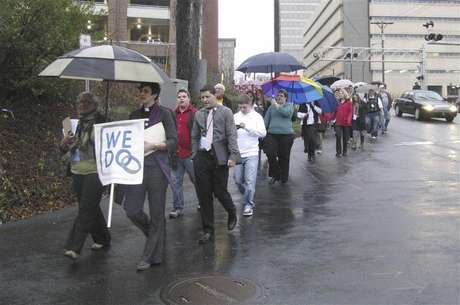 "Same-sex couples and their supporters marched through the streets of downtown Winston-Salem, North Carolina, January 14, 2013 after seeking marriage licenses that they knew they would be denied. They sang ""as long as it takes, love won't be denied"" as they walked in the rain. Holding the ""We Do"" sign at the front is Jasmine Beach-Ferrara, executive director of the Campaign for Southern Equality, which is leading the ""We Do"" push for marriage equality in seven Southern states in January. She also is a minister in the United Church of Christ. Foto: Colleen Jenkins / Reuters"