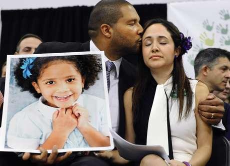 Jimmy Greene, a la izquierda, besa a su esposa Nelba Márquez Greene, mientras él sostiene un retrato de la hija de ambos, Ana, una de las víctimas de la matanaza a tiros en la escuela Sandy Hook, en una conferneica de prensa en Newtown, Connecticut, el lunes 14 de enero de 2013. Foto: AP