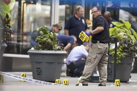 A New York Police Department officer places markers denoting spent shell casings in front of a sheet covering a body on 5th Ave after a shooting at the Empire State Building in New York in this August 24, 2012 photo. Foto: Lucas Jackson / Reuters