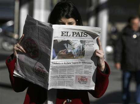 """A woman poses with a copy of the January 24 first edition of Spanish newspaper El Pais in central Madrid January 24, 2013. Spain's influential El Pais newspaper withdrew what it said was """"false photo of Hugo Chavez"""" that it had published in its on-line and print editions on Thursday. Foto: Andrea Comas / Reuters"""