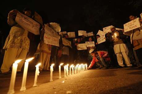 A boy places a candle as demonstrators hold placards during a candlelight march for a gang rape victim, who was assaulted in New Delhi in this file photo taken January 16, 2013. Foto: Adnan Abidi / Reuters